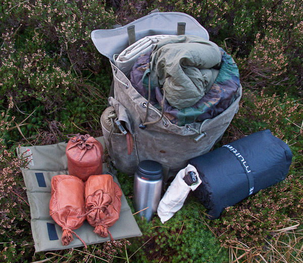 Mountain Pack-Tarp, sleeping bag, Air mat, pegs and guys, water bottle, sit mat, poncho, hobo stove and dried rations. - © 2017 - Gary Waidson - Ravenlore