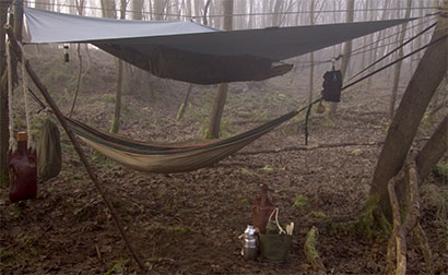 A tarp rigged on the diagonal to shelter a hammock, my usual bushcraft arrangement.