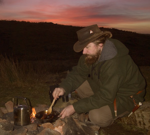 Bushcraft cooking over an open fire. A small billy can of rice boils while I brown the meat for a green curry.